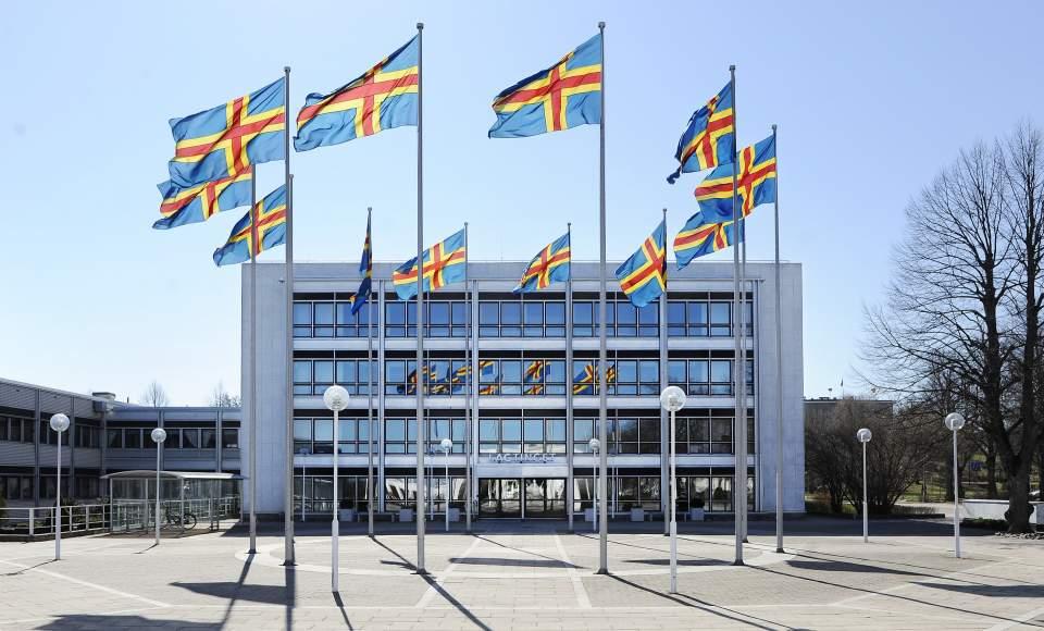 Hissade ålandsflaggor framför lagtingsbyggnaden
